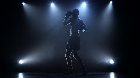 sampiyonlar : Sportsman trains to become a boxing champion. Silhouette slow motion Stok Video
