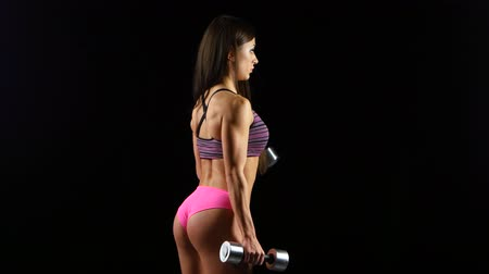 atletismo : Brutal athletic woman pumping up muscles with dumbbells Stock Footage