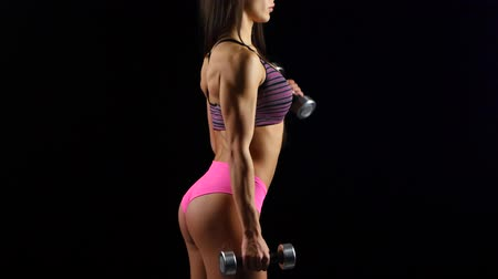 atletismo : Beautiful fitness woman with lifting dumbbells . Sporty girl showing her well trained body .