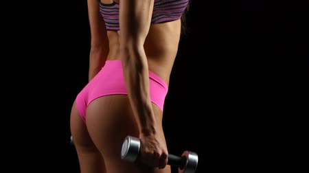 атлетика : Beautiful fitness woman with lifting dumbbells . Sporty girl showing her well trained body . Well-developed muscles by strength training .
