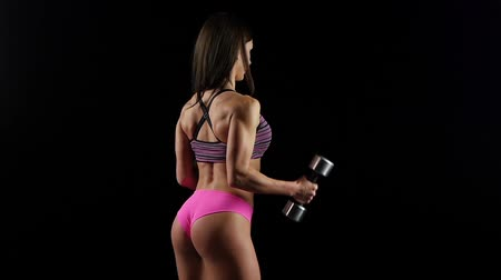 atletismo : Beautiful fitness woman with lifting dumbbells . Sporty woman lifting light weights. Fit girl exercising building muscles. Slow motion.