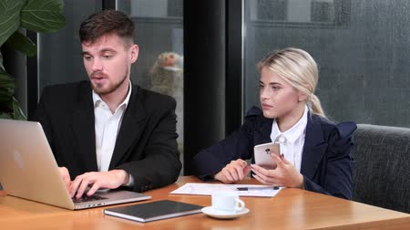 reconcile : Two office workers reconcile their data sitting in the cafe Stock Footage