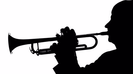 enstrümanlar : Silhouette trumpeter playing a slow tune on a pipe Stok Video