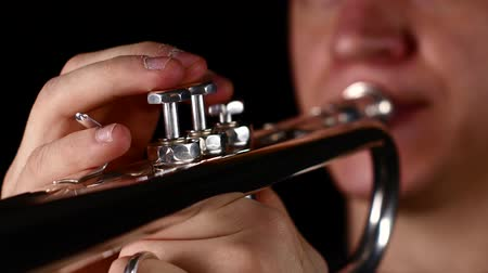 instrumento : Fingers of man pushing button on trumpet. Black background studio