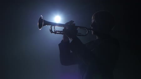 trombeta : Trumpeter plays a wind instrument fast melody. Studio in smoke
