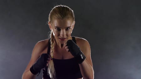 boxe : Sportswoman boxer runs towards the camera makes the blows
