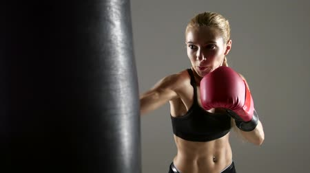 equipamentos esportivos : Beautiful boxer girl has an attempt on punching bag. Studio