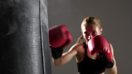 boxe : Sportswoman boxer knocks out of the punching bag. Slow motion