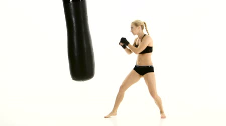 warms : Intensive training with a punching bag girl boxer. White studio Stock Footage