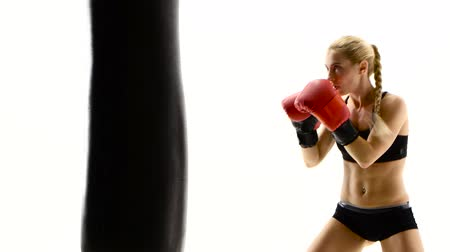 warms : Kickboxer woman fulfills blows on punching bag. White studio Stock Footage
