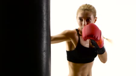 warms : Girl boxer with passion beats his fist on punching bag