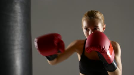 warms : Beautiful girl boxer working with a punching bag. Gray studio Stock Footage