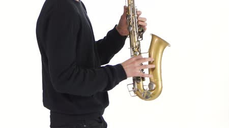 jazzman : Solo saxophone. Playing young musician man in a white studio Stock Footage