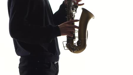 jazzman : Musician plays an old saxophone. Closeup on white background Stock Footage