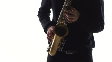 jazzman : Blues on the saxophone. Musician playing solo in white studio
