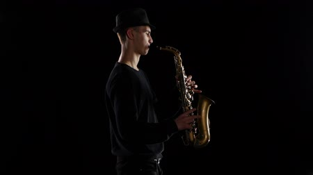 jazzman : Blues in the performance young musician saxophonist. Black background studio