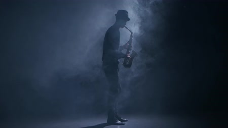 jazzman : Saxophonist playing a musical instrument in a dark smoky studio Stock Footage