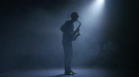 jazzman : In the spotlight musician man playing the saxophone. Smoky studio Stock Footage