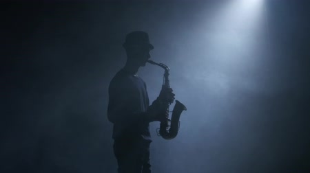 saxofonist : Saxofoon. Man-muzikant speelt een instrument in een rokerige studio Stockvideo