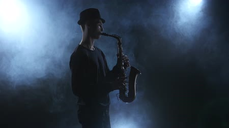 személyiség : On dark smoky studio improvisation jazz music on saxophone