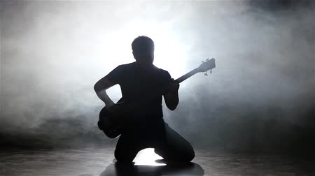 contornos : Young man bassist playing guitar on his knees. Slow motion Vídeos