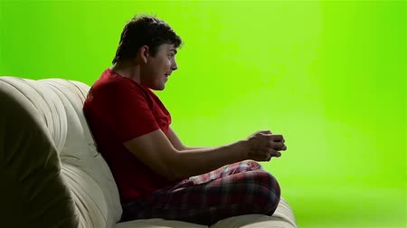 videogame screen : Gamer man intently playing a video game. Green screen studio Stock Footage