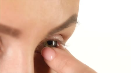 neuritis : Girl with poor eyesight removes the lens. Close up. White background. Slow motion