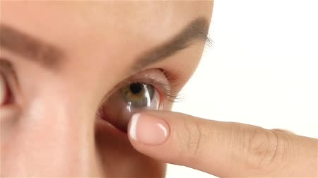 neuritis : Girl with poor vision puts lens and flashes. Close up. White background. Slow motion Stock Footage