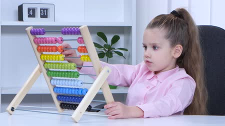 abacus : Little girl in shirt sitting at the table and said to the multicolored aba