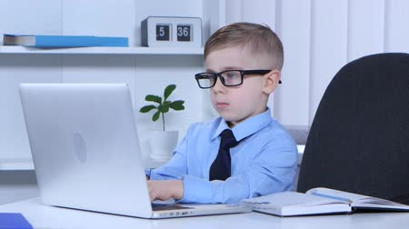 gravado : Boy in glasses is typing on a laptop and the data recorded in notes Stock Footage