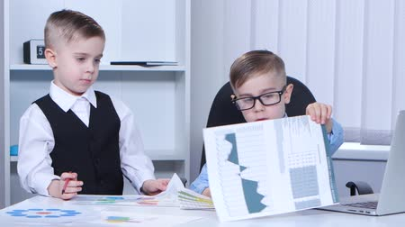 gravado : Two little boys businessman in the office consider graphs and charts