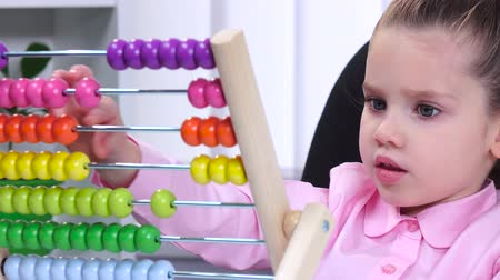 abacus : Smartest little girl in the office conducts raschty using colored wooden abacus