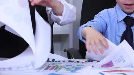 gravado : Two boys in the office on the table scatter diagram. Slow motion. Close up Stock Footage