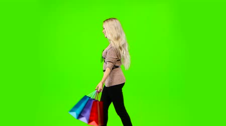 gidip : Blonde girl carries a lot of different color packages. Green screen. Side view Stok Video