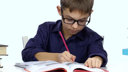 jóquei : Boy sits at a table recording something into her notebook and flips through the book. White background