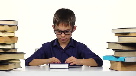 jóquei : Boy sits at a table and reading a book. White background Stock Footage