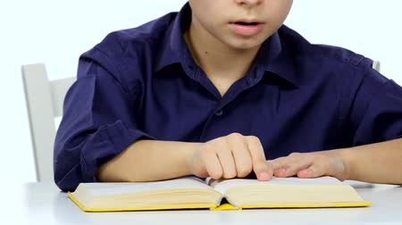jóquei : Small boy sitting at a table and reads interesting book slowly. White background. Close up