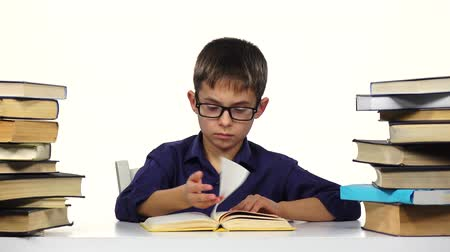 jóquei : Boy sits at the table leafing through the pages of a book. White background. Stock Footage