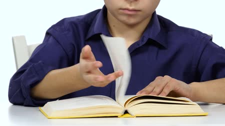 jóquei : Boy sits at the table leafing through the pages of a book. White background. Close up