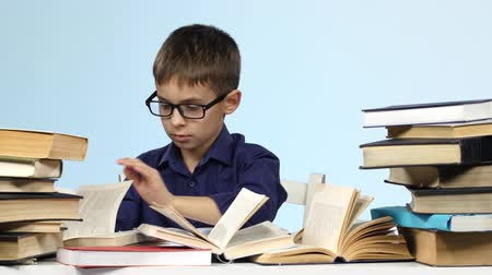 jóquei : Boy sits at the table and excitedly leafing through the pages of books. Blue background.