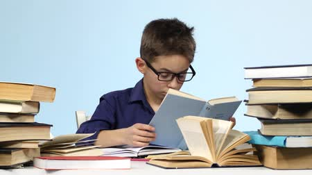 jóquei : Boy sits at the table and pull up a page with a notebook. Blue background.