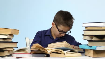 jóquei : Boy sits at the table and wearily leafing through a book. Blue background Stock Footage