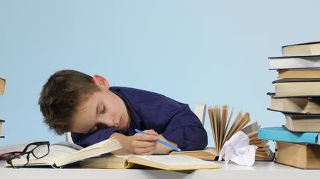 jóquei : Tired boy fell asleep at a desk between books. Blue background