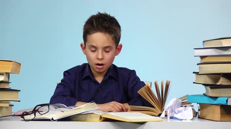 jóquei : Tired boy begins to close and fold the book. Blue background