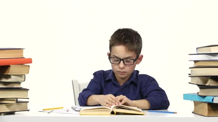 jóquei : Little boy sits at a table and reads the book slowly. White background