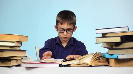 jóquei : Little boy reading a different book. Blue background. Slow motion