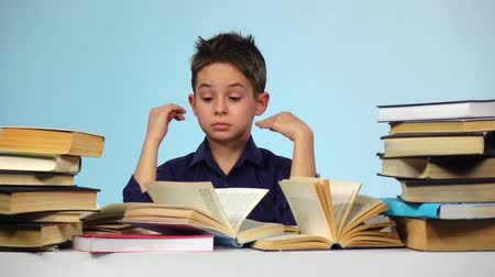 jóquei : Boy wears glasses and leafing through the book. Blue background. Slow motion