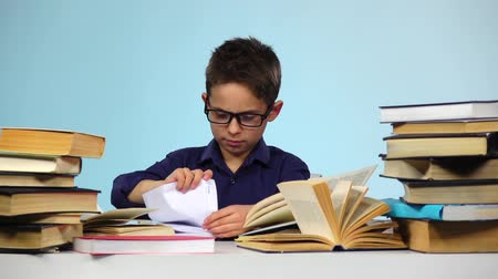 jóquei : Little boy pulls out sheets of books. Blue background. Slow motion