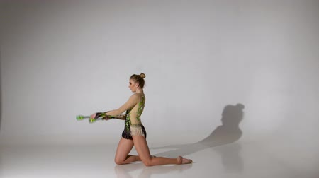 ajoelhado : Rhythmic gymnast kneeling and holding her mace it makes acrobatic movements. White background