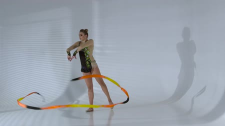 gymnasta : Rhythmic gymnast gracefully dancing with a ribbon in his hands. White background Dostupné videozáznamy